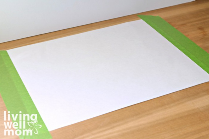 A large sheet of white paper taped to a tabletop as a canvas for finger painting.