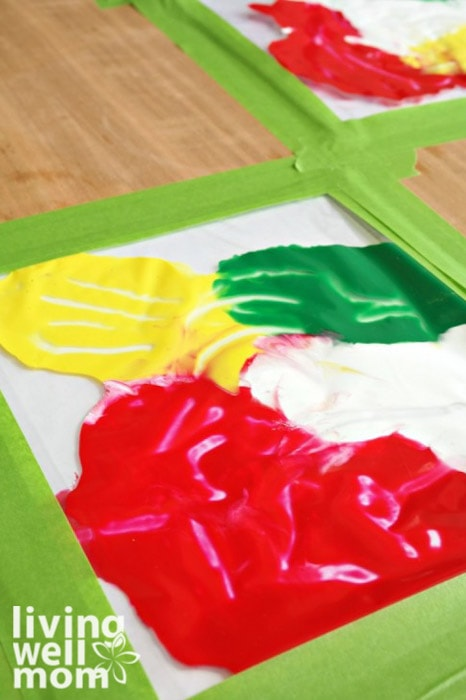 Washable paints spread around a piece of art paper inside of plastic, with toddler finger prints and tracks clearly visible.