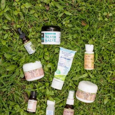 various herbal tubes and bottles for natural medicine kit on green grass