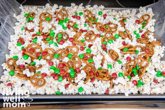 m&ms sprinkled over popcorn and pretzels