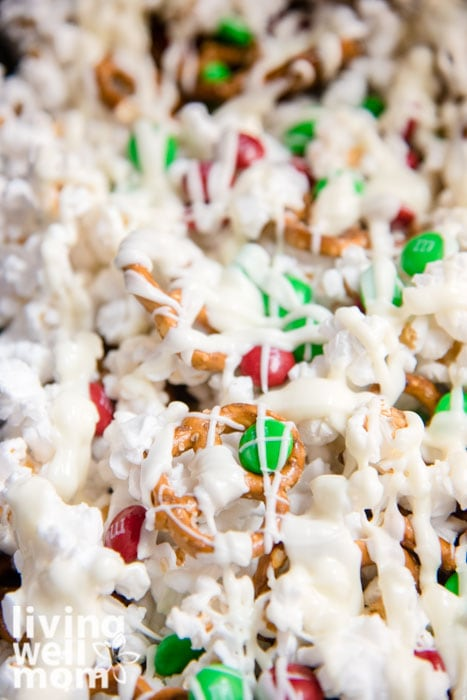 White chocolate popcorn recipe mixed with m&ms and pretzels on a baking sheet