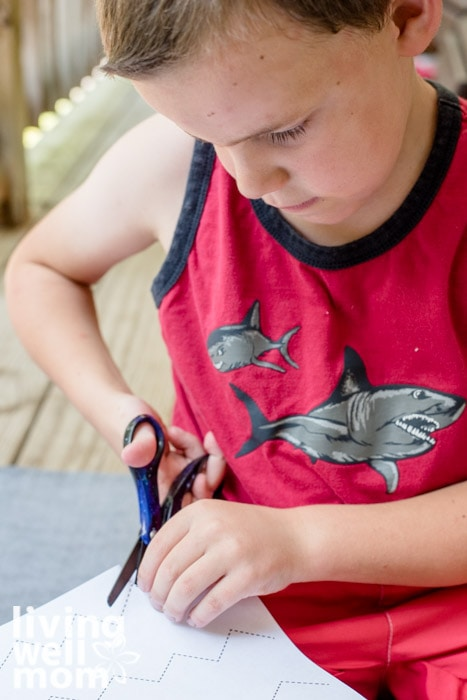 A elementary aged boy practicing scissor skills on a free printable.
