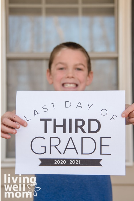 boy holding last day of third grade sign