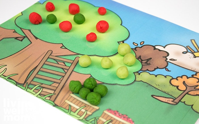 A fall themed activity mat with balls of playdough rolled up to represent apples on a tree.
