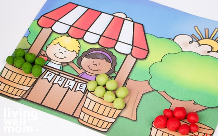 A free printable apple tree activity mat with baskets full of multicolored playdough apples.