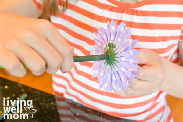 Purple flower being attached to a pen