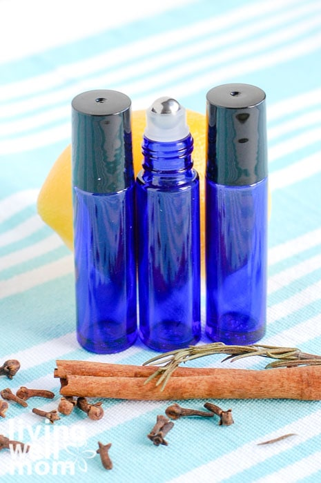 3 essential oil rollers in a row with cinnamon stick and lemon
