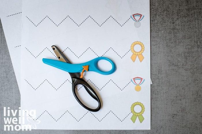 Children's safety scissors laid on top of fun and free printable scissor skills sheet.