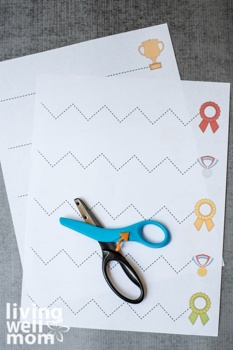 Fiskars kids scissors setting on top of printable cutting practice sheets for kids.