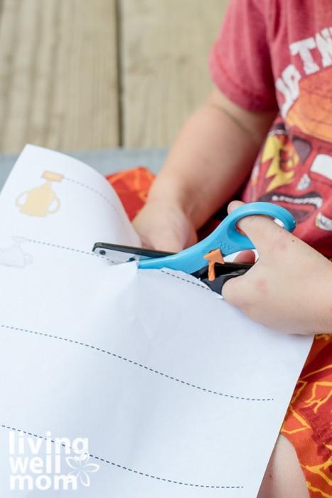 Scissor practice sheets being cut by a preschooler.