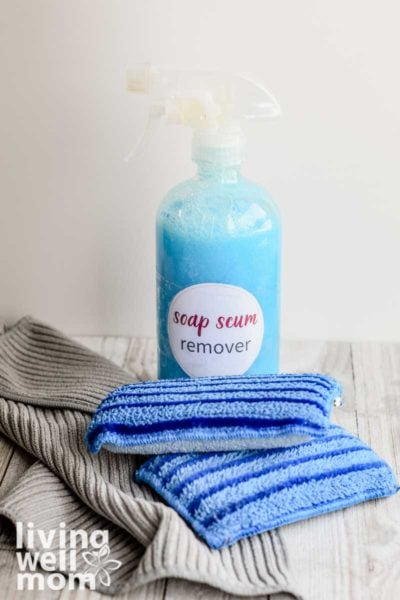 DIY soap scum remover made with soap, vinegar, lemon oil, and tea tree oil.