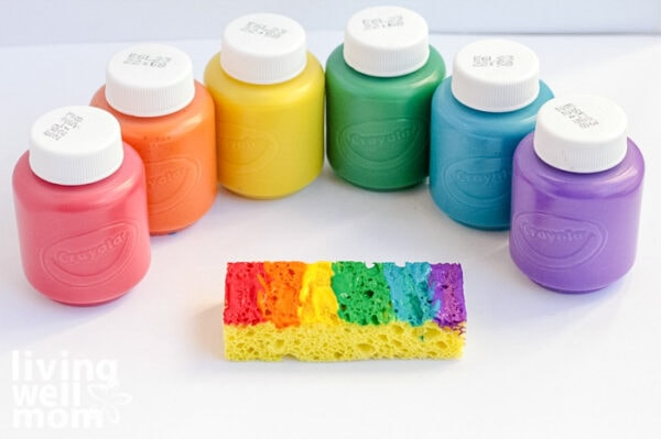 Colorful non-toxic paints fanned out next to a sponge