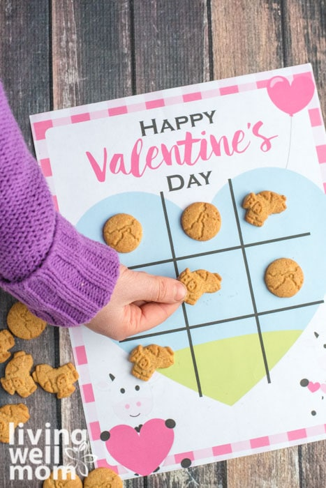 Young girl playing with a tic tack toe valentine using cookies