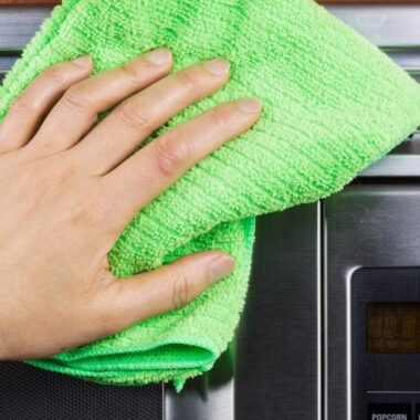 green cloth hand cleaning silver microwave