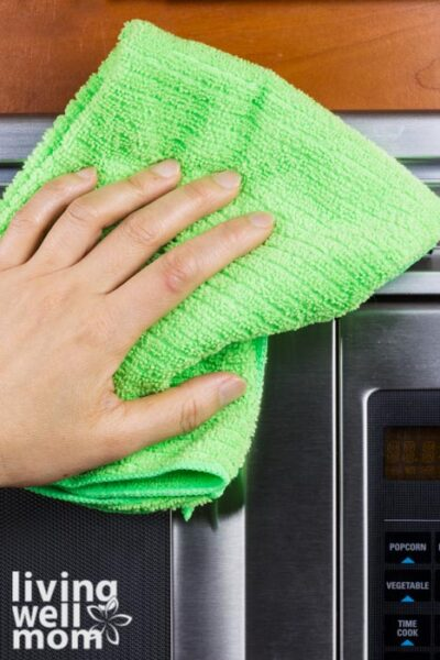 Hand with microfiber rag cleaning the outside of a microwave oven
