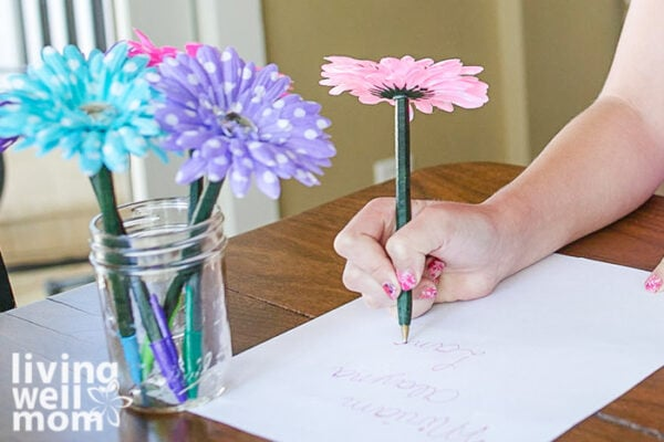 Girl writing a note with a pink flower pen
